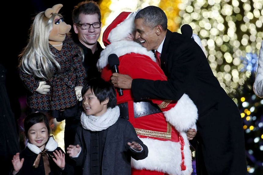 US President Barack Obama hugs a man dressed as Santa Claus as Muppets character Miss Piggy watches during the National Christmas Tree Lighting and Pageant of Peace ceremony on the Ellipse near the White House in Washington on Dec 3.