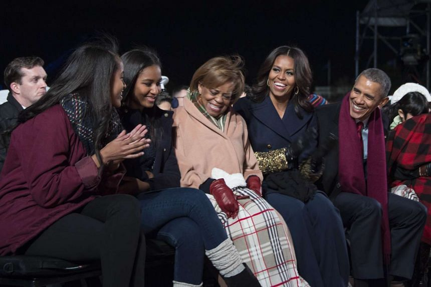 US President Barack Obama and First Lady Michelle Obama share a laugh with their daughters Malia (left) and Sasha (second left), and Marion Robinson (centre), Michelle Obama's mother, during the lighting of the National Christmas Tree event in Presid
