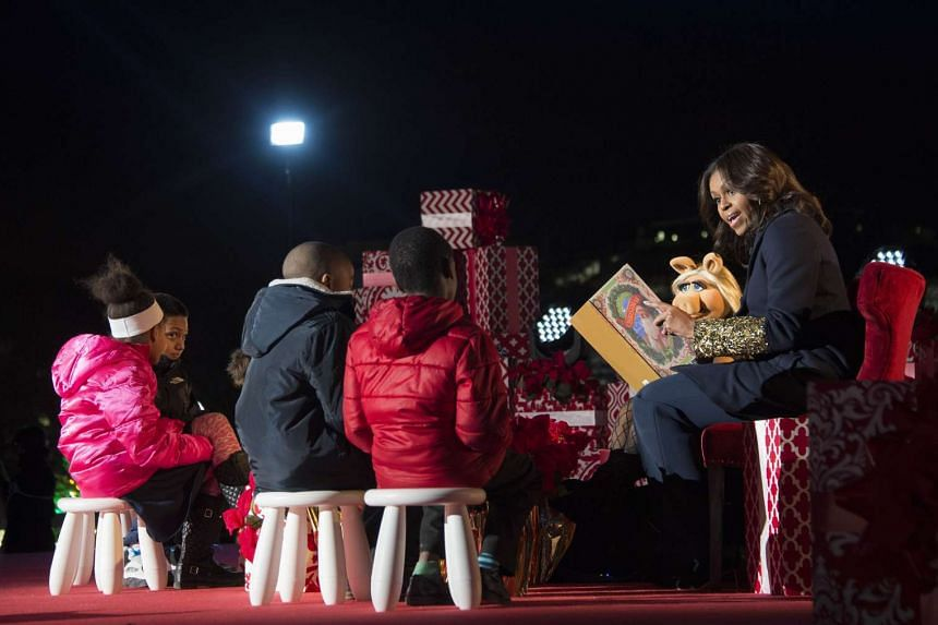 """First Lady Michelle Obama and Muppet Miss Piggy read """"Twas the Night Before Christmas"""" to children after lighting the National Christmas Tree in President's Park outside the White House in Washington, DC, on Dec 3."""