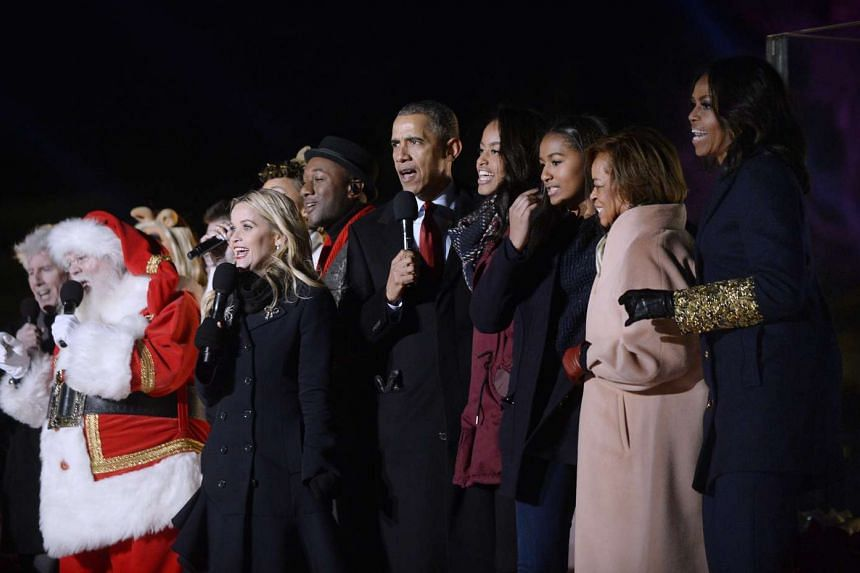 US President Barack Obama and daughters Malia and Sasha, mother-in-law Marian Robinson, first lady Michelle Obama and actress Reese Witherspoon sing from the stage during the national Christmas tree lighting ceremony near the White House in Washingto
