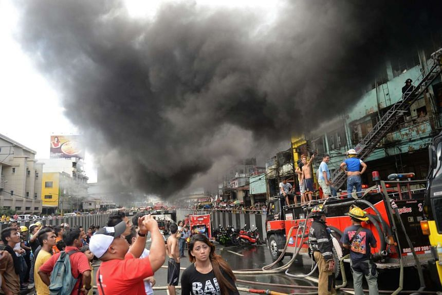 Thick black smoke engulfs streets and buildings after a fire.