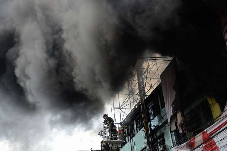 A fireman stands on a truck ladder amidst thick black smoke engulfing streets and buildings after a fire.