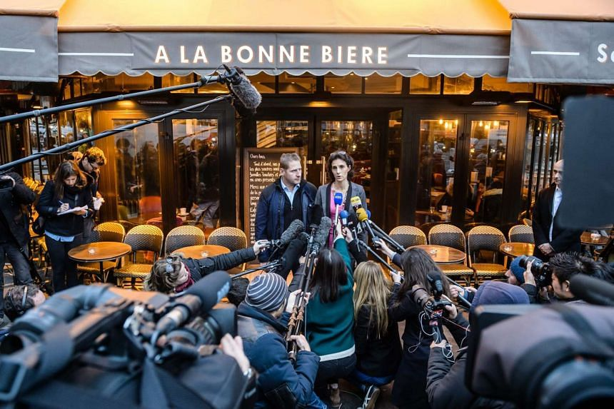 Cafe managers Audrey Bily (Right) and Romain Debray, speak to media outside the cafe during its reopening.