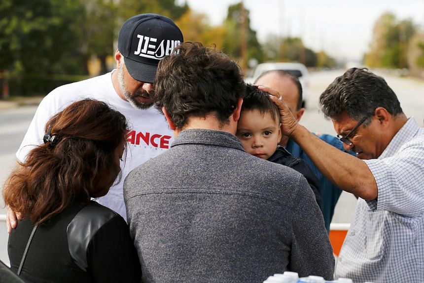 Neighbours comfort a family who were prevented by police from returning to their home near the scene of a mass shooting in San Bernardino on Dec 3.
