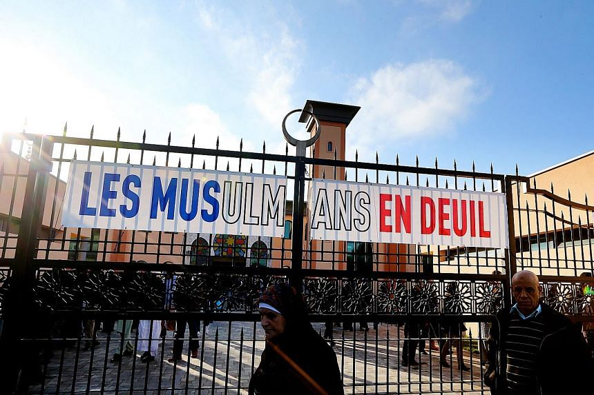 "People walk past a banner that reads ""Muslims in mourning"" as they leave the Reims mosque after the Friday prayer on Nov 27."