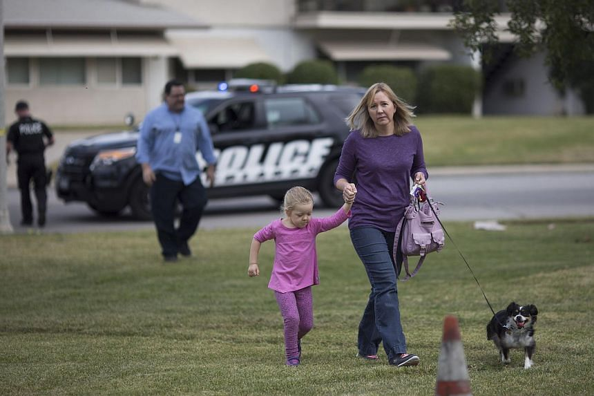 Neighbors of Syed Rizwan Farook and Tashfeen Malik walk to their home behind police lines to retrieve items after a mass shooting on Dec 3, 2015.