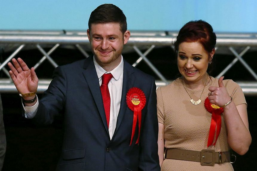 Labour Party candidate Jim McMahon gestures as he stands with his partner Charlene Duerden after winning the Oldham West and Royton by-election following the count at the Civic Centre in Oldham.