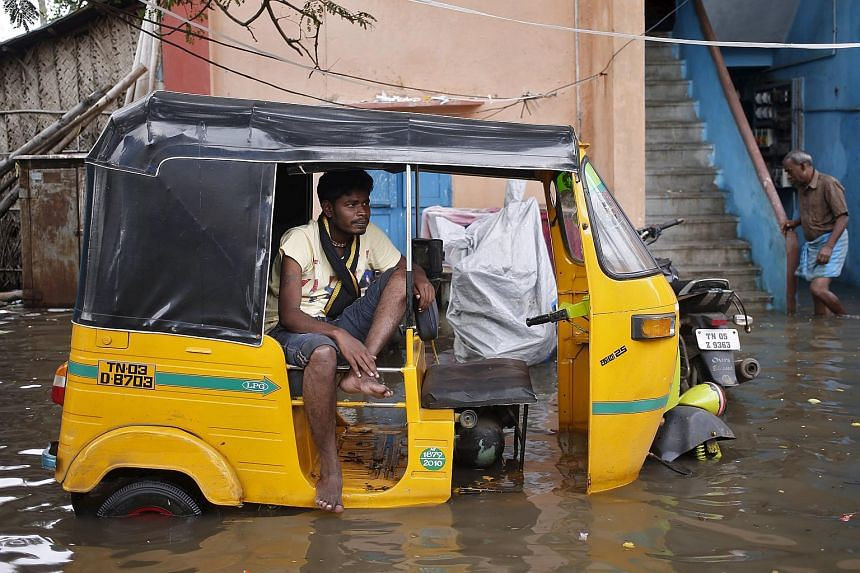 A man sits in an auto-rickshaw in a flooded area in Chennai, India, on Dec 3.