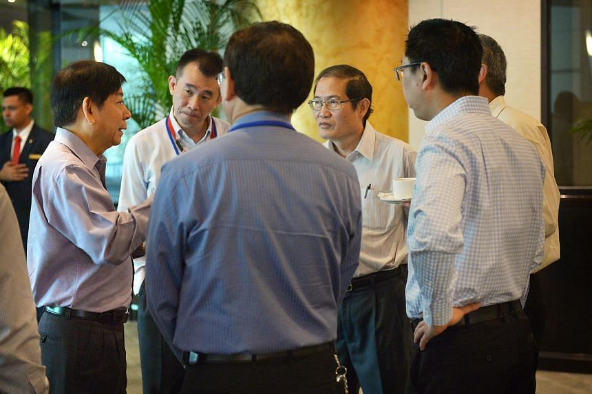 Minister for Transport Khaw Boon Wan (left) chats with officials and engineers before the signing of the MOU on joint infrastructural maintenance between LTA, PUB, SMRT and SBST held at the Grand Copthorne Waterfront hotel on Dec 4.
