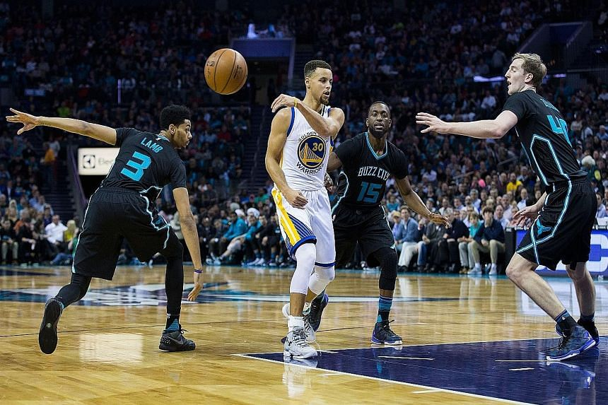 Stephen Curry (30) making a no look pass as Jeremy Lamb (3), Kemba Walker (15) and Cody Zeller (40) take him on.