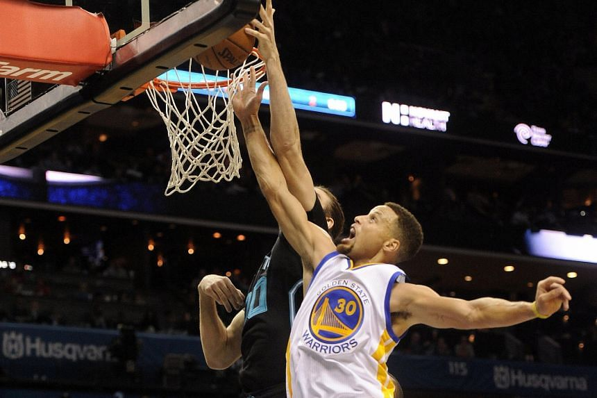 Stephen Curry (right) fighting for a rebound against Charlotte Hornets. He finished as Golden State Warriors' top scorer for the fifth straight game in the 116-99 win.