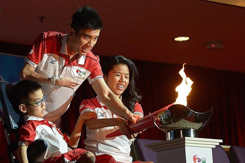 From left: Nine-year-old boccia player Aloysius Gan, badminton player Tay Wei Ming and swimmer Yip Pin Xiu combining to light the Asean Para Games' cauldron at the Singapore Indoor Stadium last night.