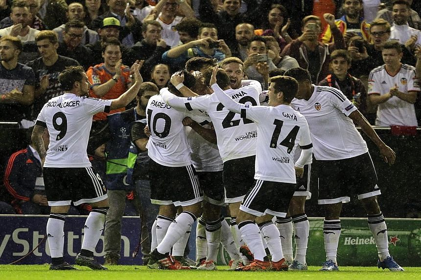 Valencia players celebrating a goal in their 2-1 Champions League win over Ghent in October. The Spanish team must beat Lyon on Wednesday and hope the Belgian side do not overcome Russian Group H winners Zenit in order to make the round of 16.