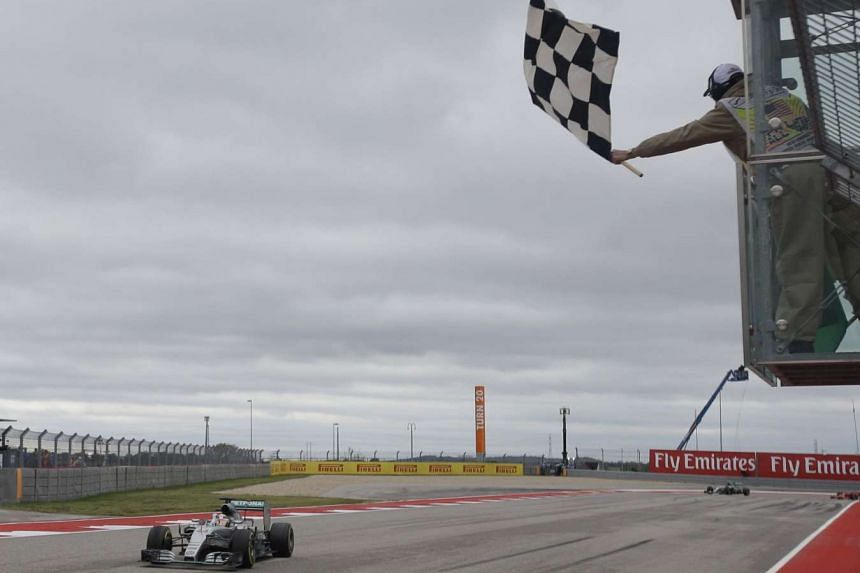 Mercedes driver Lewis Hamilton crosses the finish line to win the Formula One US Grand Prix auto race at the Circuit of the Americas on Oct 25, 2015, in Austin, Texas.