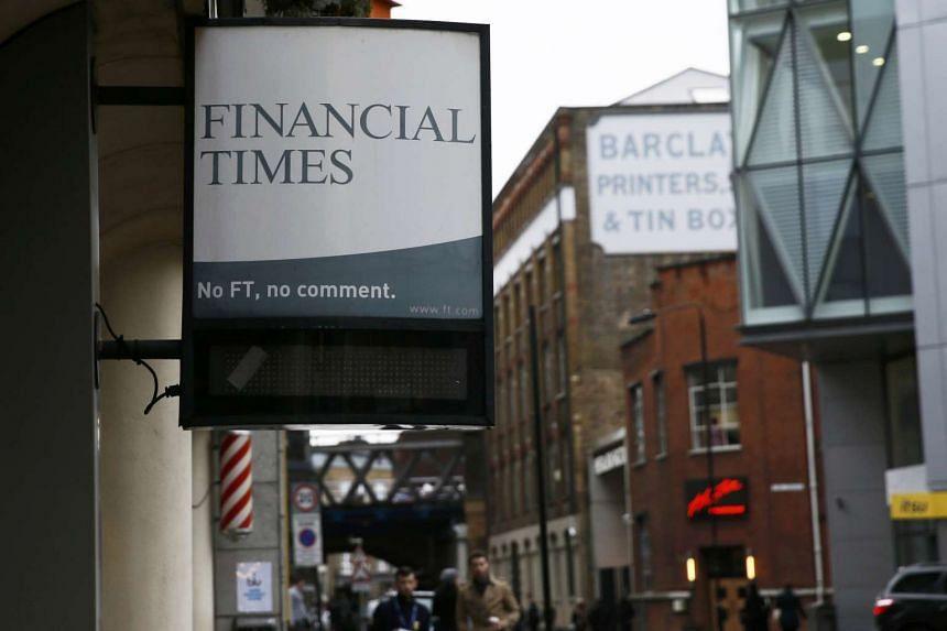 A Financial Times newspaper board hangs outside a newsagents in London.