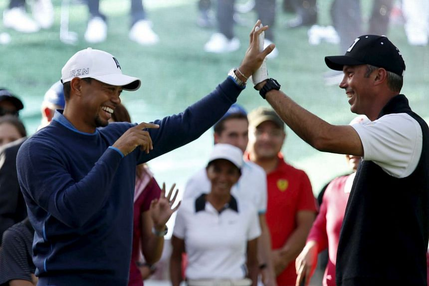 US golfer Tiger Woods high fives with compatriot and fellow golfer Matt Kuchar during a golf clinic in Mexico City on Oct 20.