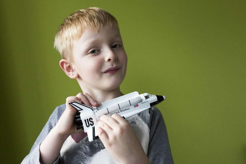 Oliver Giddings at home with a model space shuttle.