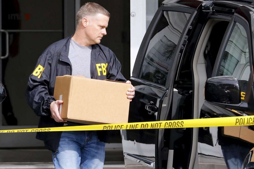 FBI agents remove boxes and other items from the offices of Imagina in Miami, Florida.