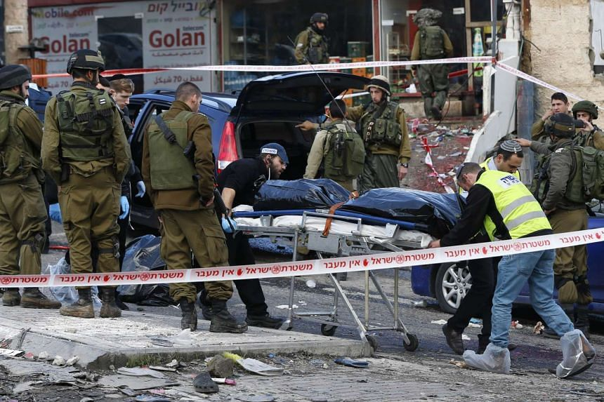 Israeli security forces and forensics transport the body of the alleged Palestinian assailant.