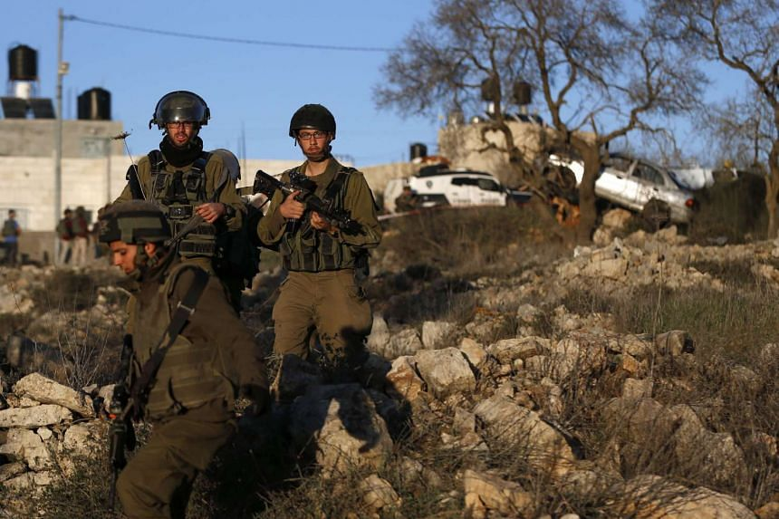Israeli soldiers walk at the site where a Palestinian driver ran over and injured two Israeli soldiers.