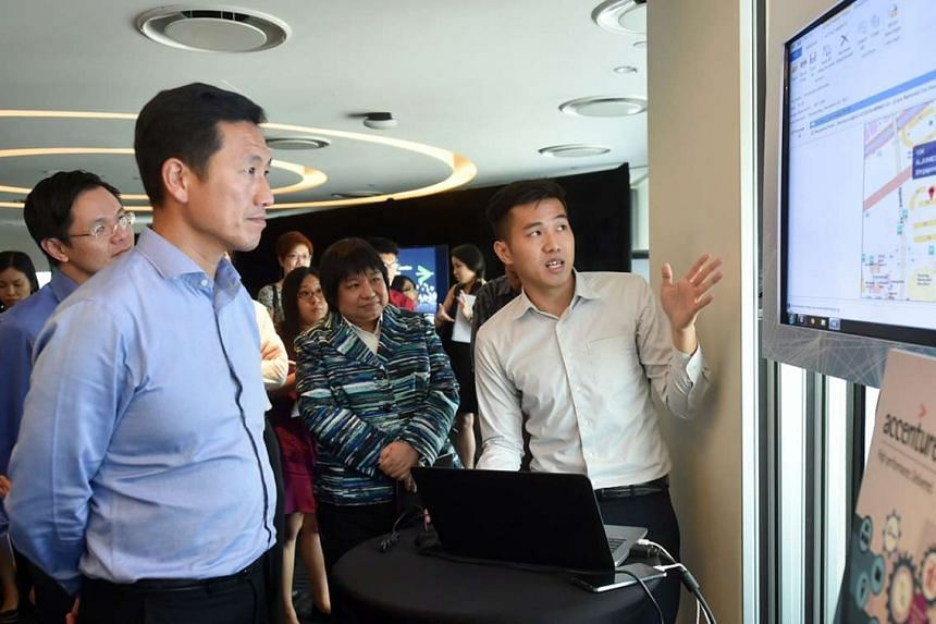 Poly graduate Ong Jia Ming giving a presentation to Acting Minister for Education Ong Ye Kung at Accenture's office yesterday.