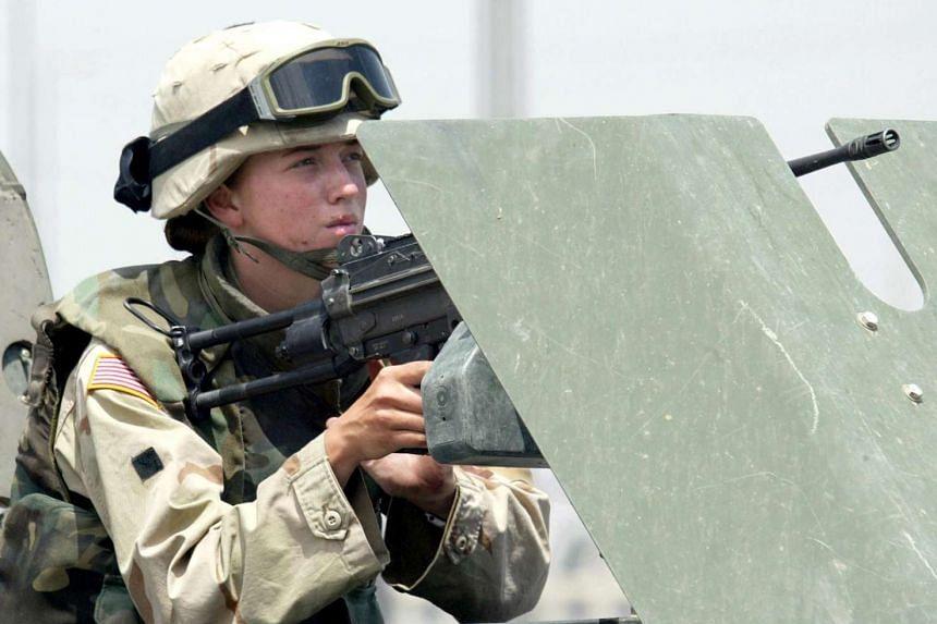 A female US soldier manning a machine gun in the Iraqi city of Mosul in 2003.