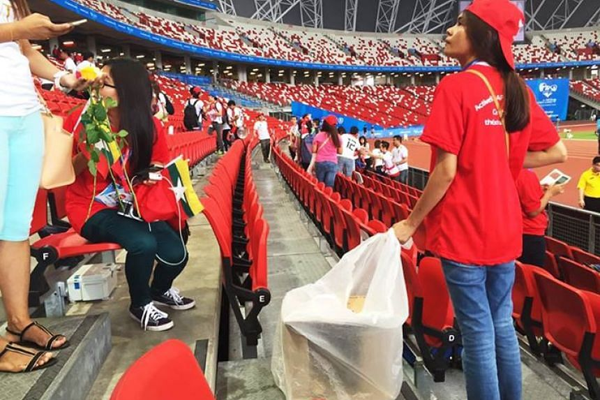 A Myanmar fan picking up litter along the seats after the match.