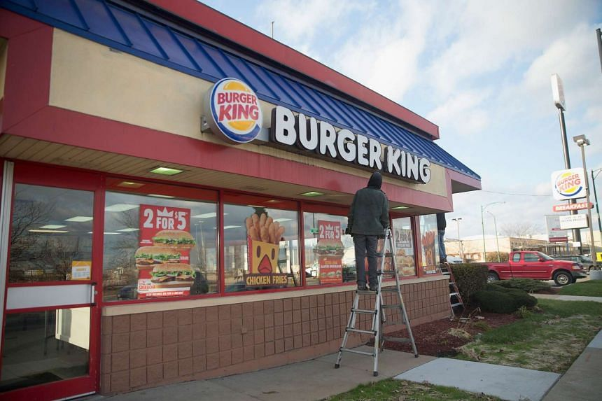 A worker repairs a sign on a Burger King restaurant on the city's Southwest side in Chicago, Illinois.