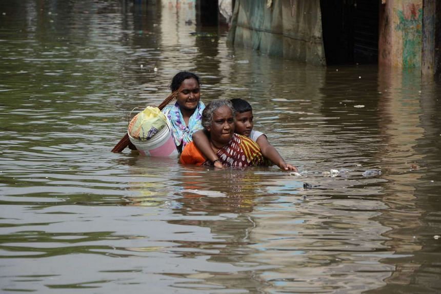 Indian people walk through through floodwaters on a street in Chennai.