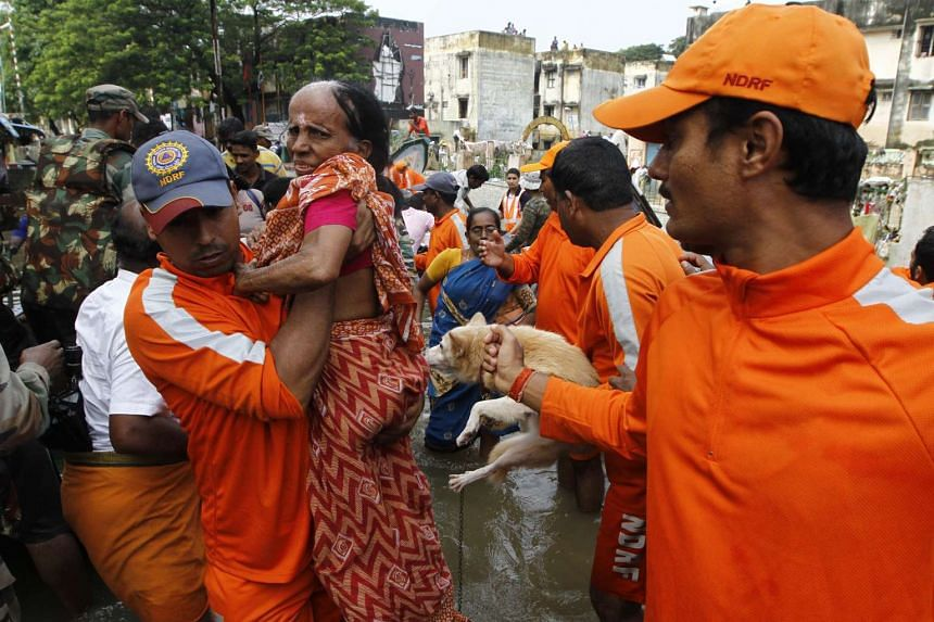 National Disaster Response Force personnel carry an elderly woman rescued from floodwaters.