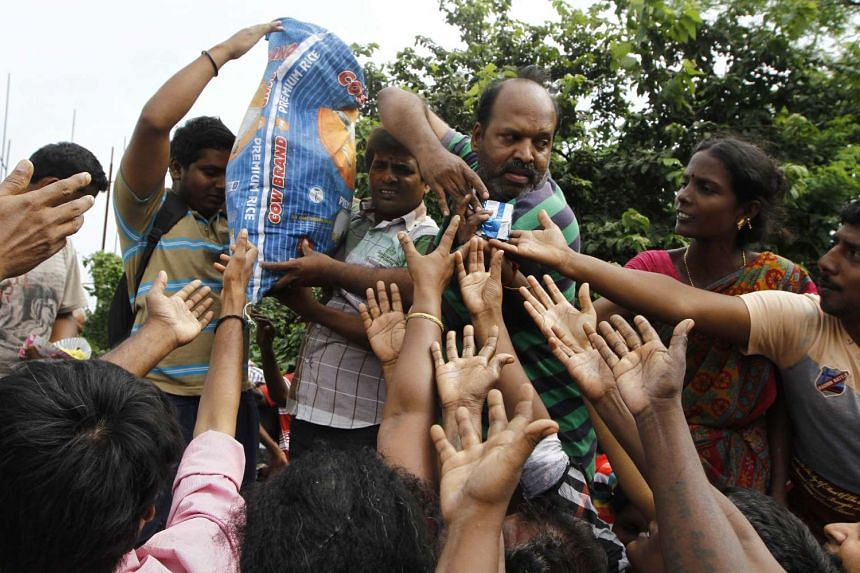 Flood-affected people stretch out their hands to receive packets of biscuits being distributed.