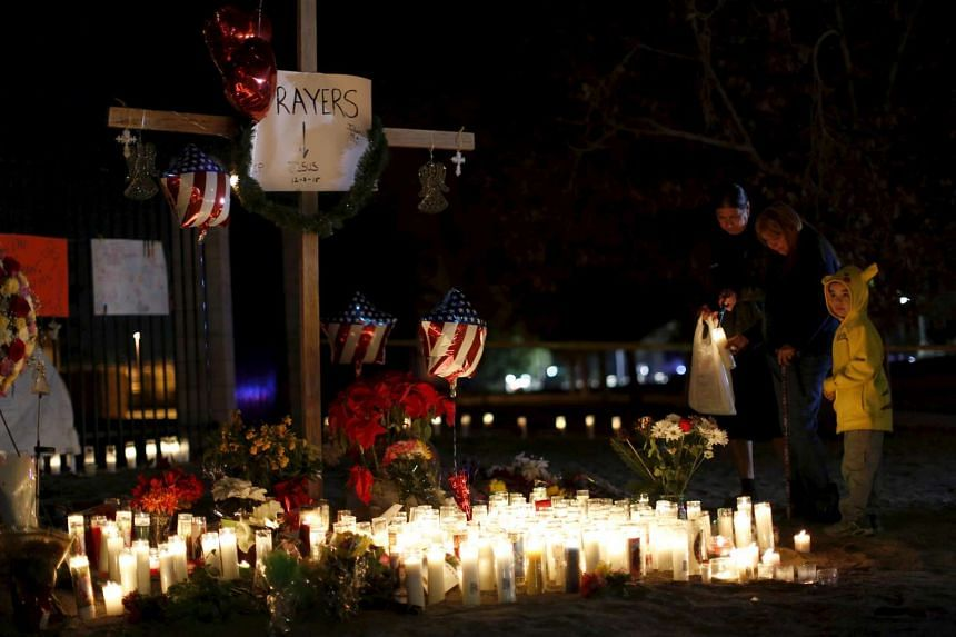 People stand by a pop-up memorial in San Bernardino, California.