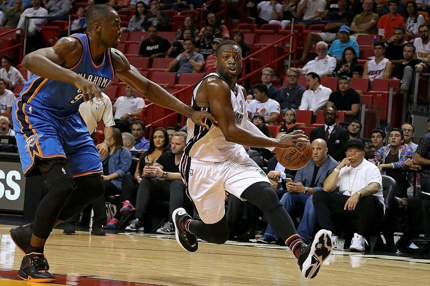 Dwyane Wade (right) accelerates past Oklahoma City Thunder's Serge Ibaka as the 33-year-old taps on his experience to lead Miami Heat out of a tight spot. His two free throws nailed the win with 1.5 seconds left.