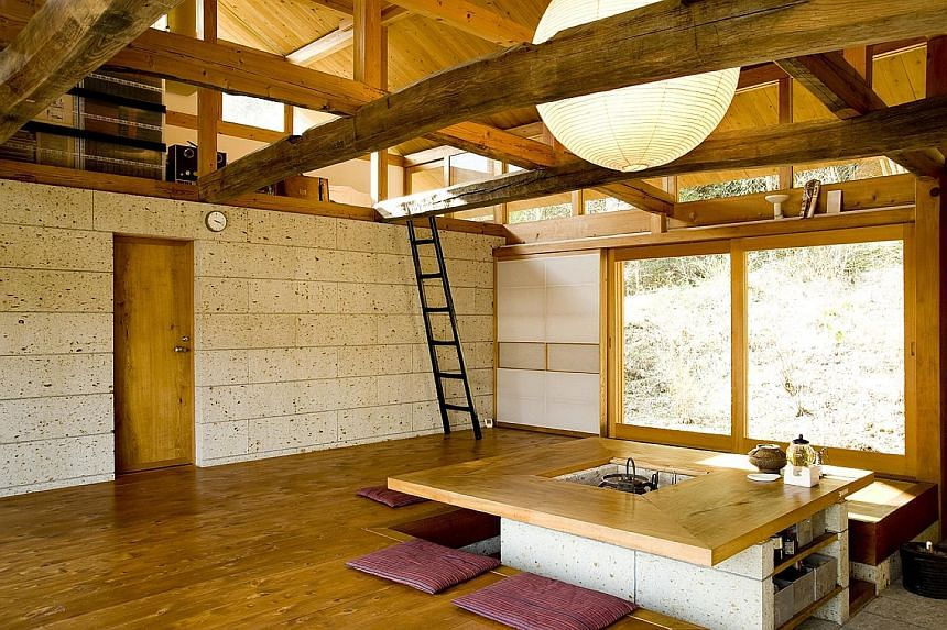 The living room of architect Minoru Matsuzawa has exposed beams. Located in Tochigi, a Japanese prefecture north of Tokyo, the house was built using materials such as oya stone, a local volcanic material, and timber from the forest behind it.