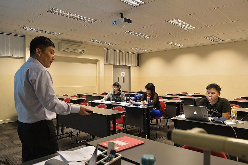 Former M2 students (from left) Ho Yuet Ching, 25, Yii Yieng Hong, 26, and Leon Lee, 25, attending a lesson on consumer protection conducted by former M2 lecturer Francis Ho, 40, at PSB Academy last month.