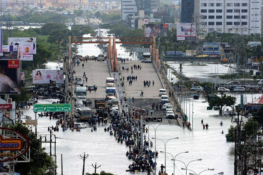 Chennai residents gathering on a flyover in the flood-hit city. Despite rescue efforts by the military and civilian emergency services, help has yet to reach many areas.