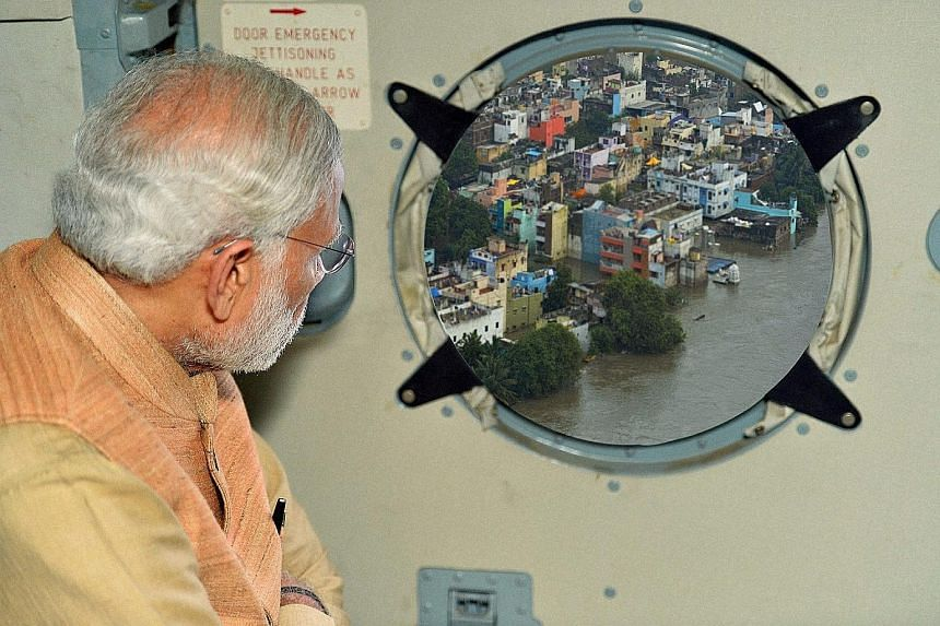 An undoctored photograph (top left) showing Prime Minister Narendra Modi surveying an area of rain-hit Chennai was posted on his Twitter feed. The Press Information Bureau also published on its website a similar photo (bottom) with a much clearer ima