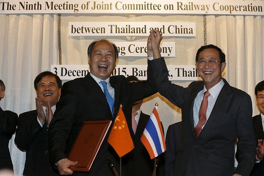 Mr Wang Xiaotao (left), the deputy head of China's National Development and Reform Commission, and Thai Transport Minister Arkhom Termpittayapaisith (right) celebrating the railway construction agreement. The deal underlines the warming ties between