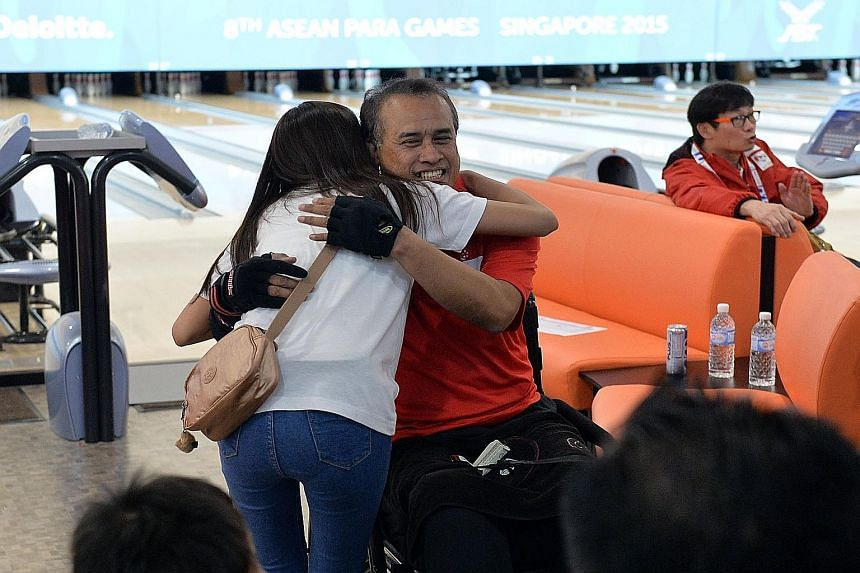 Clockwise from left: Singapore's Anuar Saaid being hugged by his daughter Khairiah Anuar, 25, who was at the Temasek Club to support him. Singapore's Mohamad Ismail Hussain retained his TPB3 crown. Mohamad Rausyan, a Para Games debutant, won the TPB4