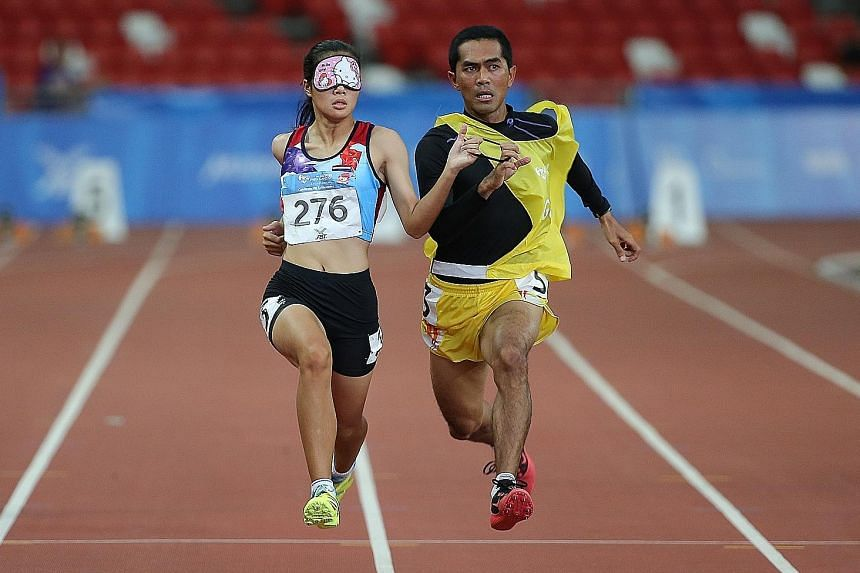 Thailand's Wannaruemon Kewalin running alongside her guide as she is visually impaired. The 21-year-old broke the Games record in the women's 100m T11 event.