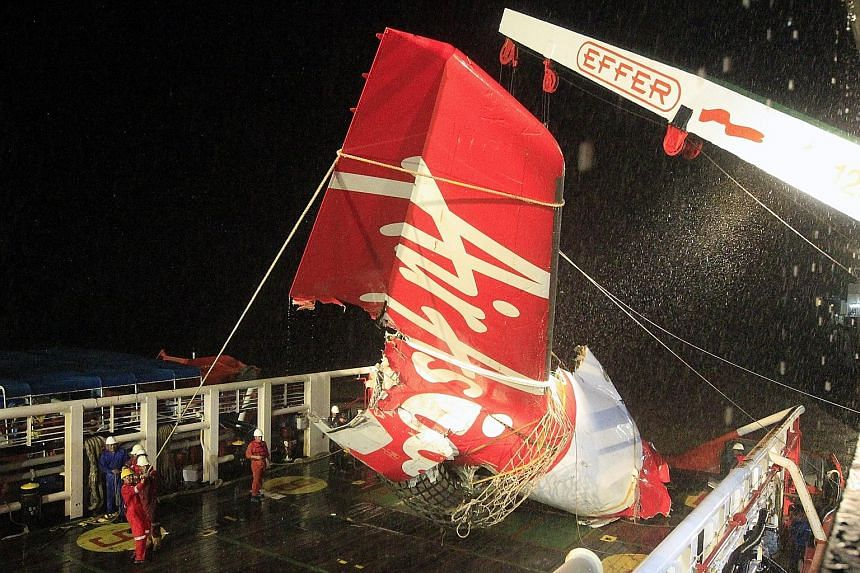 """An Indonesian search and rescue crew recovering the tail of Flight QZ8501 from the Java Sea in January. The lawsuit filed by the families claims the plane's rudder trim limiter was """"subject to failure""""."""