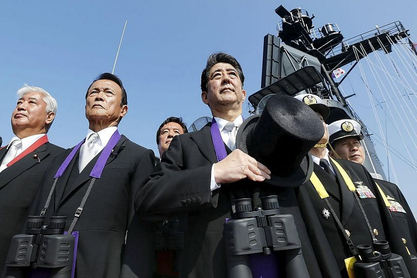 Japanese Prime Minister Shinzo Abe (far right) reviewing the Japan Maritime Self-Defence Force fleet with Deputy Prime Minister and Finance Minister Taro Aso (centre) and Defence Minister Gen Nakatani at Sagami Bay, south of Tokyo, on Oct 18.