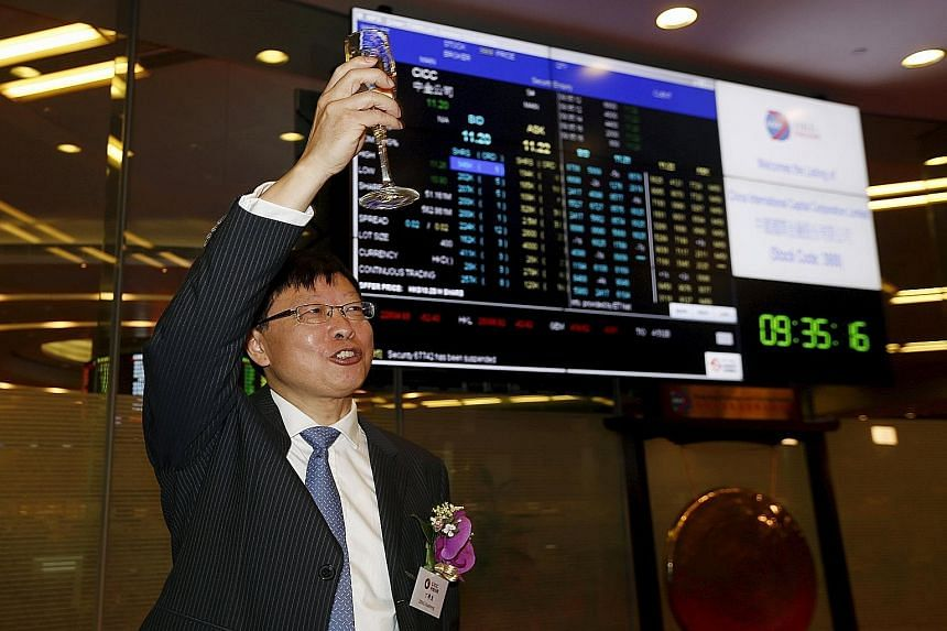 China International Capital Corp (CICC) chairman Ding Xuedong celebrating during the debut of CICC at the Hong Kong stock exchange in Hong Kong on Wednesday.