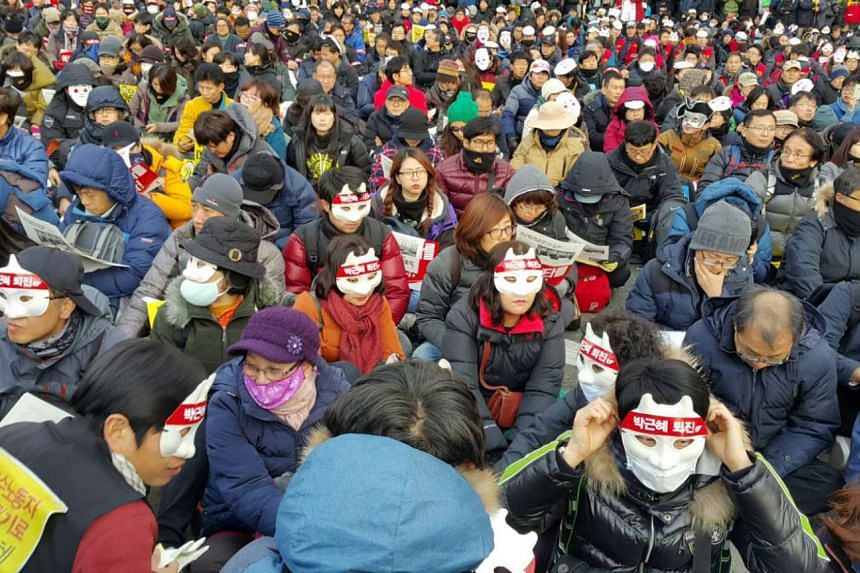 """Protesters seated at Seoul Plaza on Dec 5, 2015, wearing masks with the words """"Park Geun Hye resign""""."""