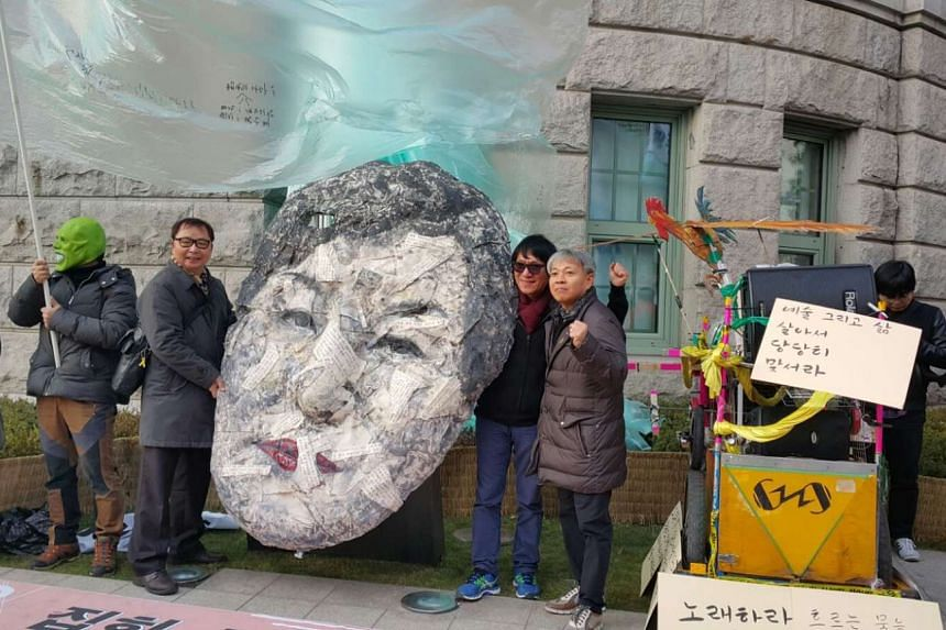 Some protesters holding a giant paper mask of President Park Geun Hye's face