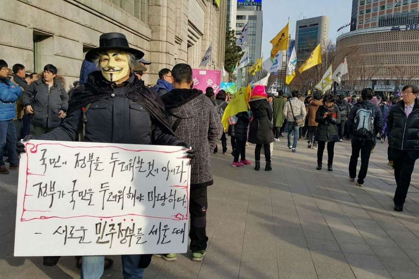 Masked protester holding a sign that says: The government should be afraid of the people, people should not be afraid of the government.