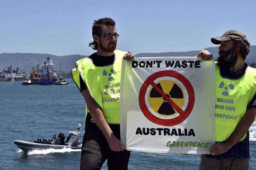 Greenpeace activists holding a placard as a ship (top left) transporting reprocessed nuclear waste arrives at Port Kembla in New South Wales on Dec 5.
