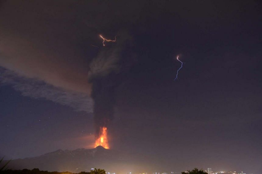Lightning is visible in the clouds as Mount Etna spews lava and hot ash, as seen from Catania, Italy.