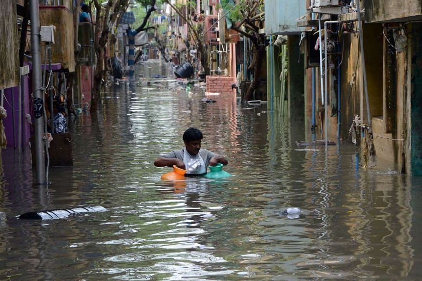 A man carrying gas canisters through floodwaters on a street in Chennai.