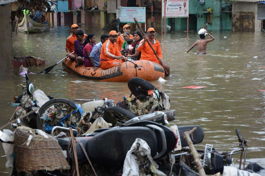 Indian rescue workers transporting residents through floodwaters in Chennai.